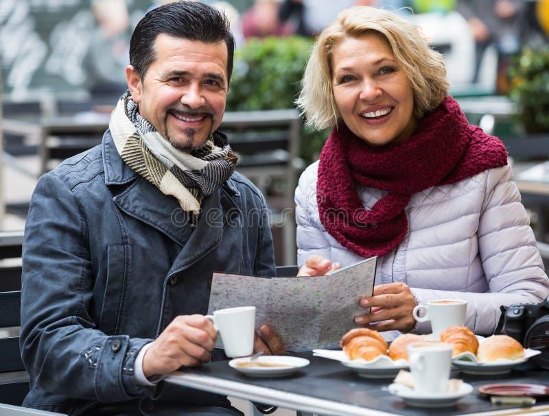 Turister som har kaffe på kafé- och läsningöversikten royaltyfri bild