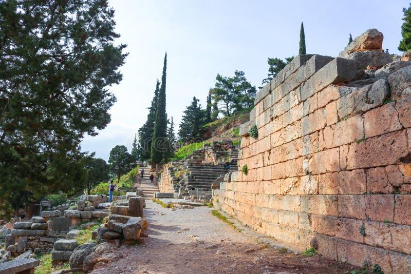 Turister som igenom går och tar bilder av, fördärvar på forntida Delphi Greece med väggar och trappa och träd fotografering för bildbyråer