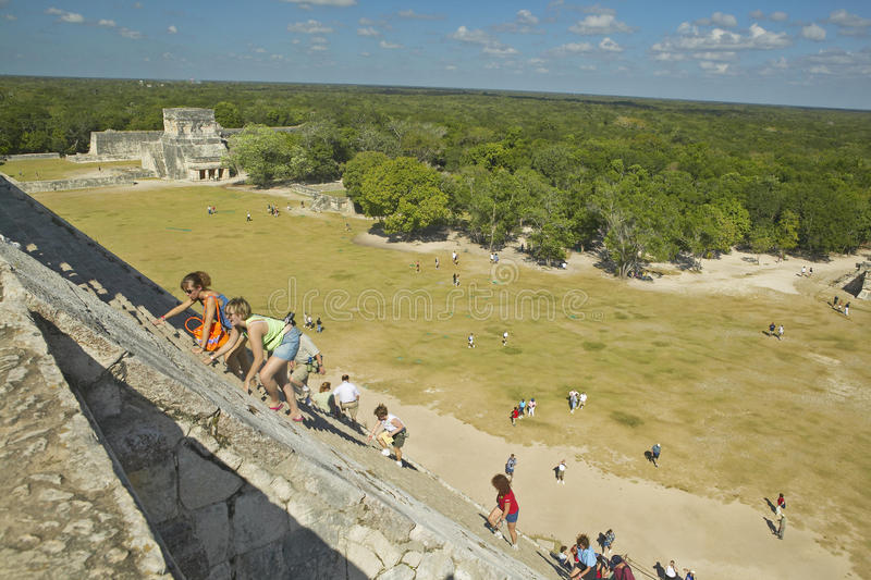 Turister som klättrar den Mayan pyramiden av Kukulkan (också som är bekant som El Castillo) och fördärvar på Chichen Itza, den Yu royaltyfria foton