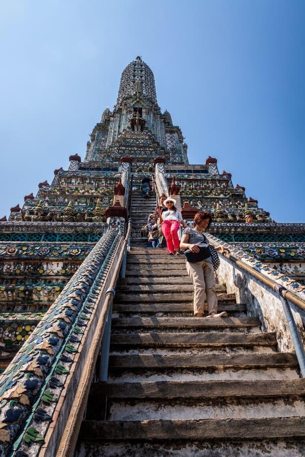 Turister som klättrar upp och går ner på brant trappa av den Wat Arun templet royaltyfria bilder