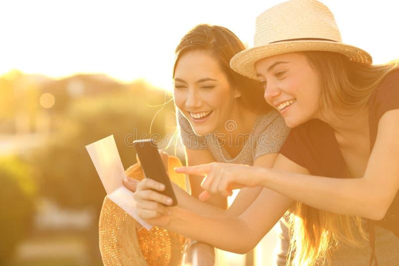 Turister som kontrollerar information på linje på solnedgången royaltyfri bild