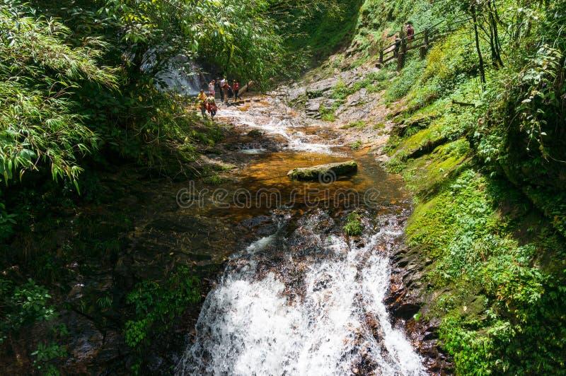 Turister som korsar den snabba bergfloden i guld- strömecotouri fotografering för bildbyråer