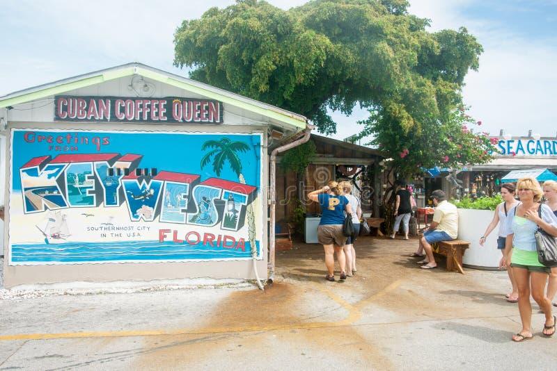 Turister som passerar det kubanska drottningkafét nära strand med signagen för hälsningkort på byggnad royaltyfria foton