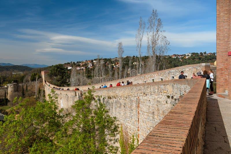 Turister som promenerar de medeltida stadsväggarna i Girona, Catalonia, Spanien arkivbild