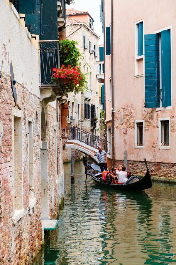 Turister som rider en gondol på en liten kanal som omges av gamla byggnader i Venedig arkivfoton