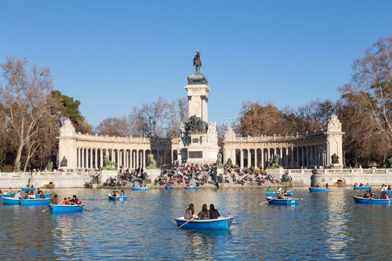 Turister som ror traditionella blåa fartyg på sjön i den Retiro staden, parkerar på en trevlig solig vinterdag i Madrid, Spanien royaltyfria bilder