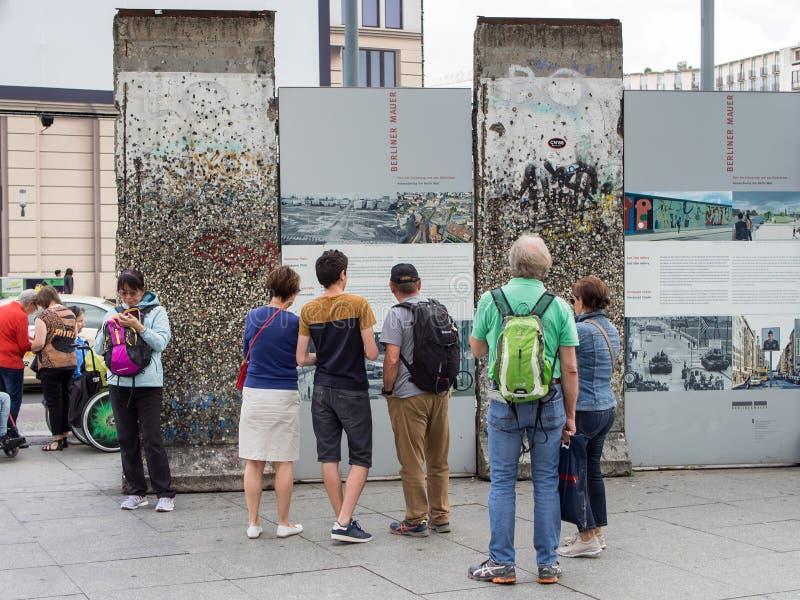 Turister som ser en del av gamlan Berlin Wall At Potsdamer Platz i Berlin arkivfoton