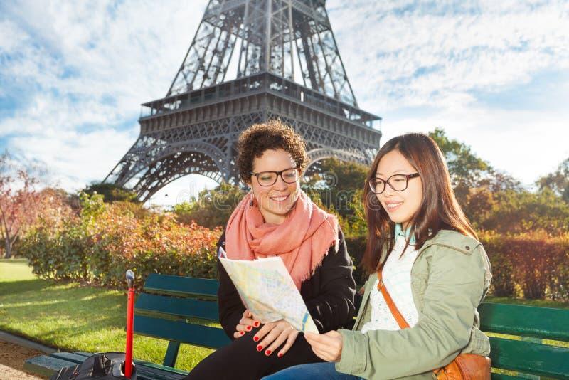 Turister som ser för att kartlägga nära Eiffeltorn arkivfoto