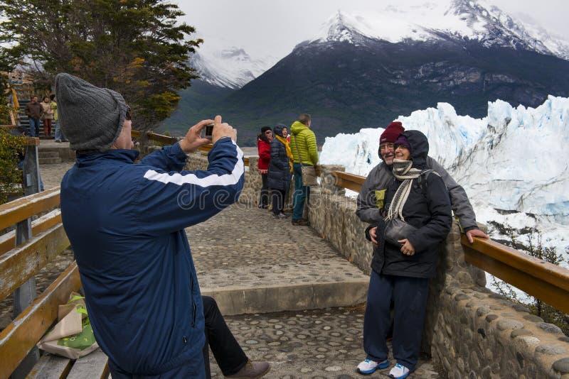 Turister som ser Peritoen Moreno Glacier i nationalparken för Los Glaciares, Patagoniaregion, Argentina royaltyfri fotografi