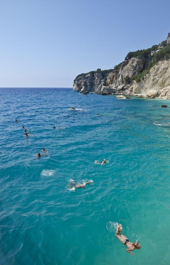 Turister som simmar i turkosvatten arkivbild