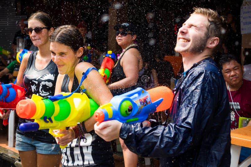 Turister som skjuter vattenvapen på den Songkran festivalen i Bangkok, Th royaltyfri bild