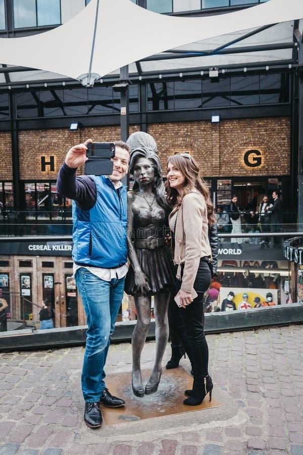 Turister som tar foto med den Amy Winehouse statyn i Camden, London, UK royaltyfri fotografi