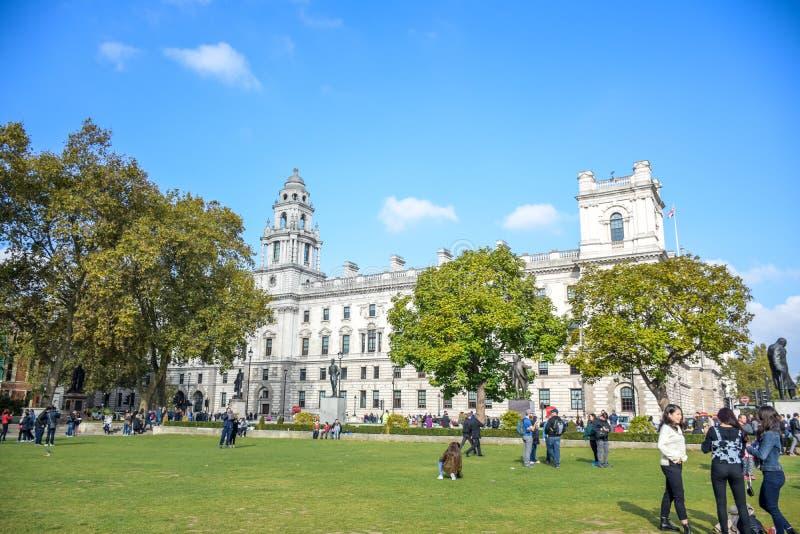 Turister som tycker om deras tid på Parliament Squareträdgården i centrala London, England arkivbild