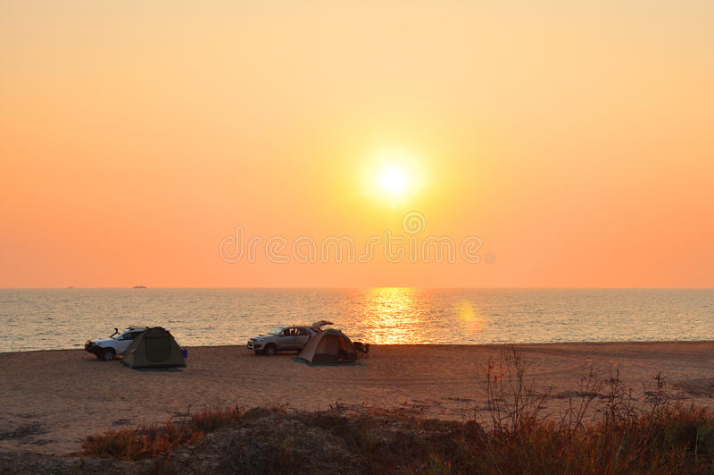 Turister som tycker om en härlig solnedgång på stranden royaltyfri fotografi
