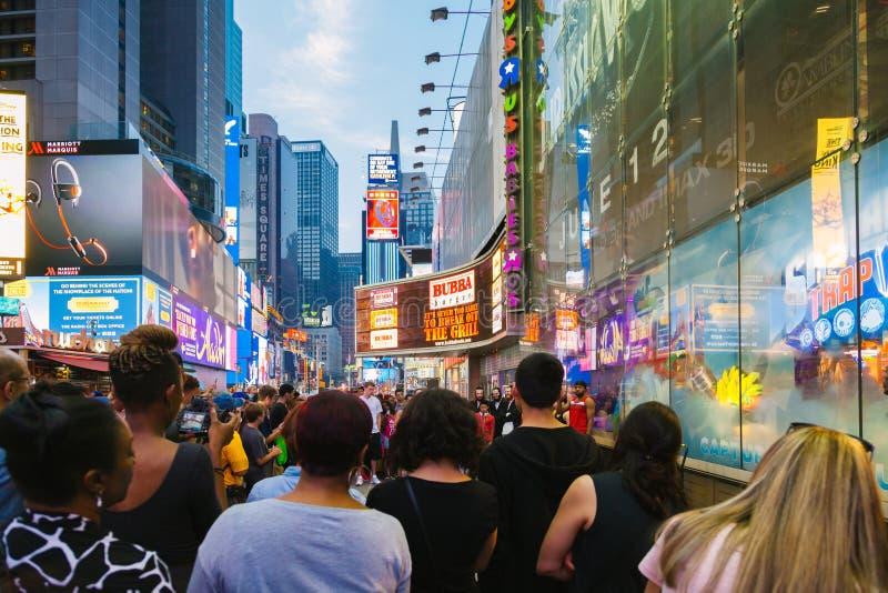 Turister som tycker om en kapacitet i Time Square, New York fotografering för bildbyråer