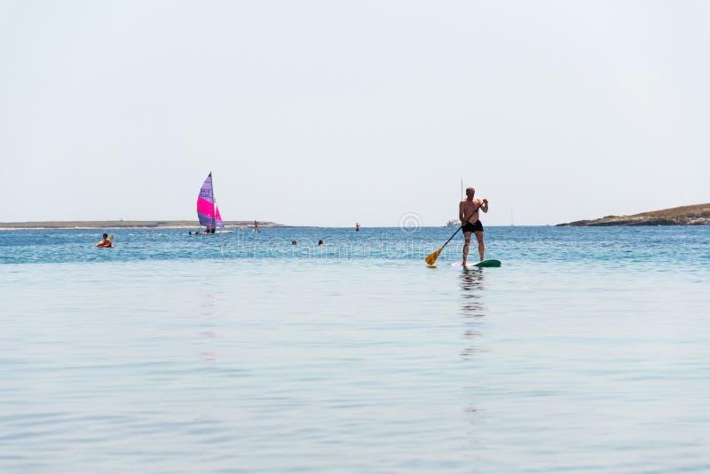 Turister som vindsurfar och paddleboarding runt om den Kamenjak halvön vid Adriatiskt havet i Premantura, Kroatien arkivbild