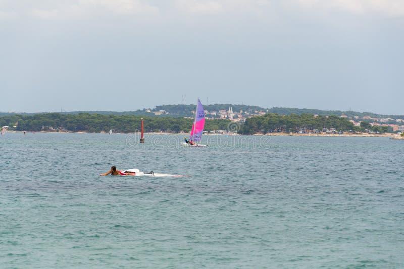 Turister som vindsurfar och paddleboarding runt om den Kamenjak halvön vid Adriatiskt havet i Premantura, Kroatien arkivfoton
