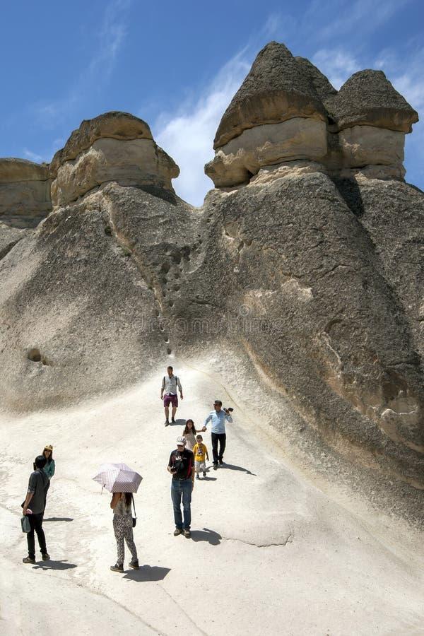 Turister står nära en trio av felika lampglas arkivfoto