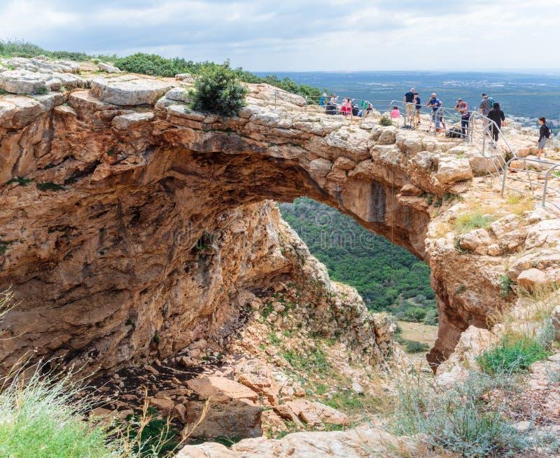 Turister står och ser den Keshet grottan - den forntida naturliga kalkstenbågen som spänner över restna av en grund grotta med at royaltyfri foto