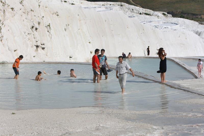 Turister tycker om travertinesna på Pamukkale royaltyfri fotografi