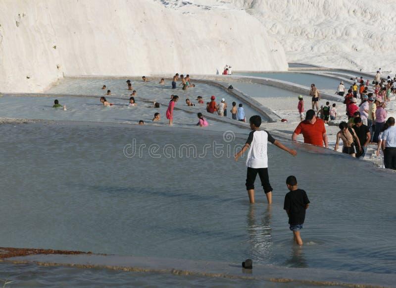 Turister tycker om travertinesna på Pamukkale fotografering för bildbyråer