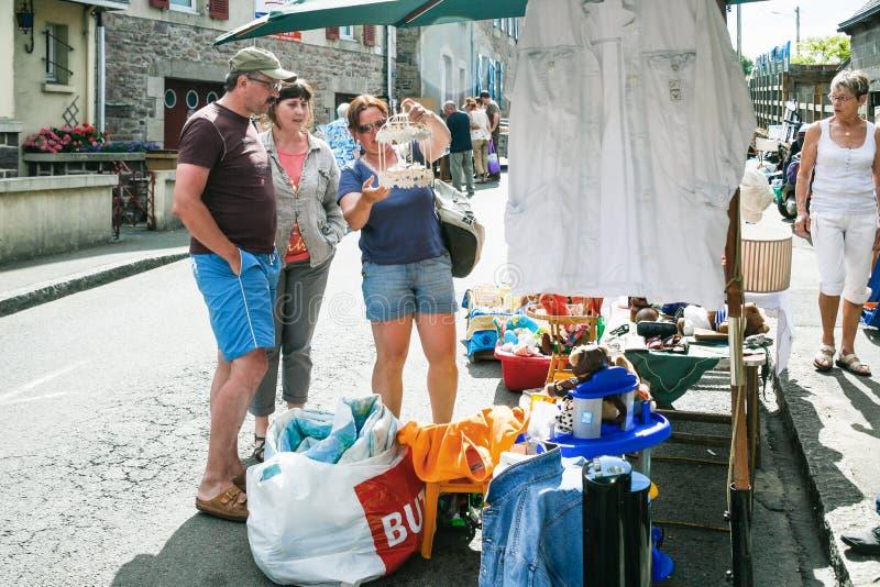 Turister väljer en goda på loppmarknad i Paimpol fotografering för bildbyråer