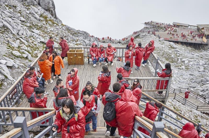 Turister vilar på vägen upp till den Jade Dragon Snow Mountain visningplattformen royaltyfri fotografi