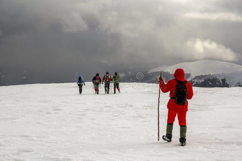 Turistfotvandrare i vintersnö täckte berg och dramatisk cl arkivfoto