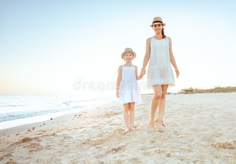Turisti adatti felici del bambino e della madre sulla spiaggia nella sera immagine stock