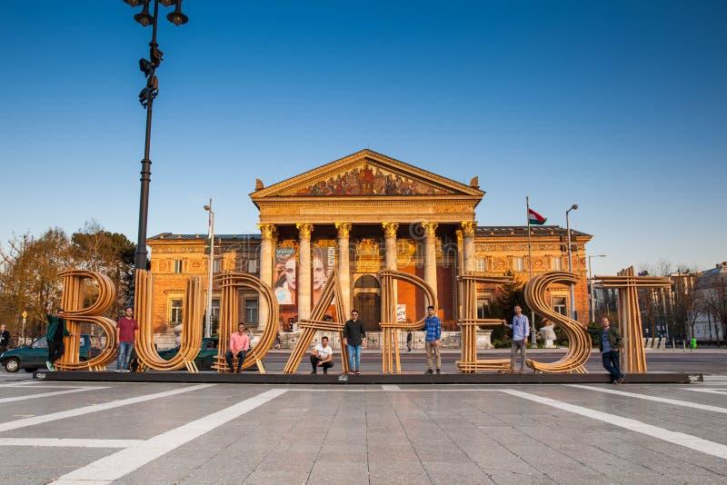 Turisti al segno della città di Budapest e Budapest Corridoio di arte su fondo fotografia stock libera da diritti