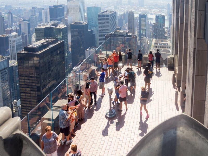 Turisti alla cima della piattaforma di osservazione della roccia a New York CIT immagini stock