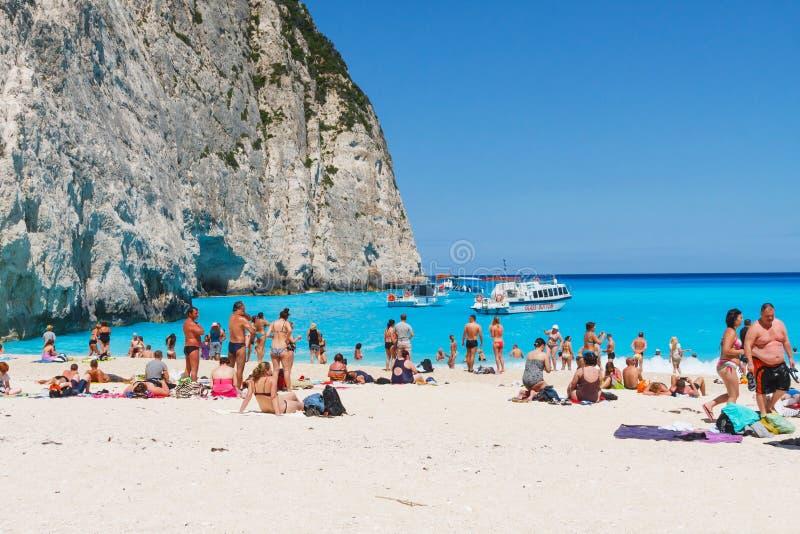 Turisti alla spiaggia di Navagio in Zacinto, Grecia immagine stock