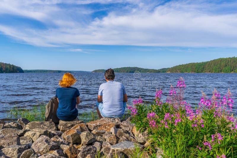 Turisti bruno e giovane donna della testarossa che si siede sulle pietre sulla riva della baia del lago nella sera soleggiata di  fotografia stock libera da diritti