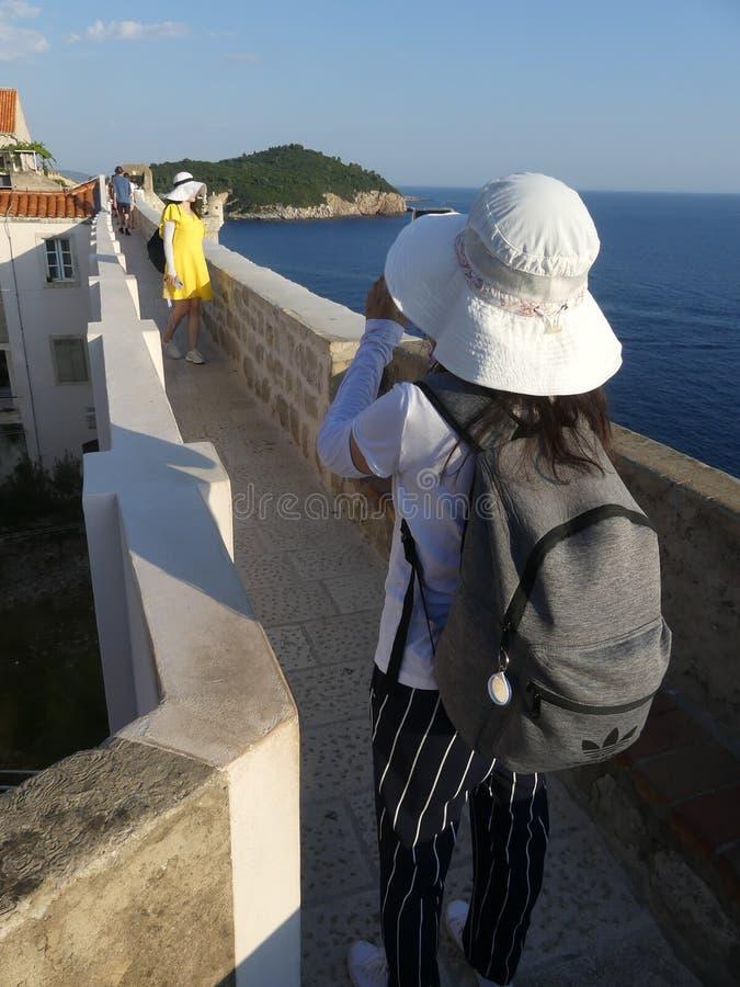 turisti che camminano lungo il muro di Dubrovnik, città vecchia, con cappelli solari dai colori vivaci fotografia stock libera da diritti