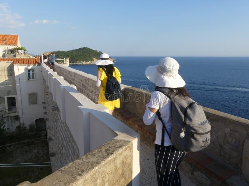 turisti che camminano lungo il muro di Dubrovnik, città vecchia, con cappelli solari dai colori vivaci fotografie stock libere da diritti