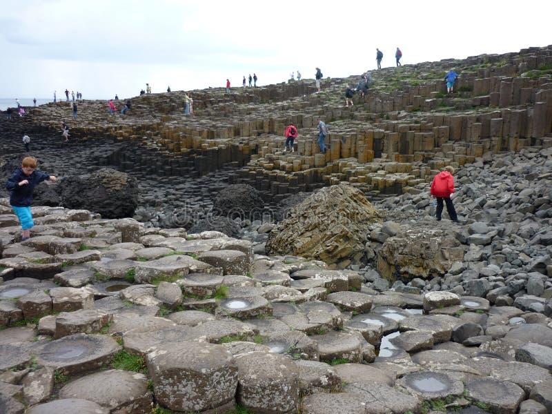 Turisti che camminano sulle colonne del basalto della strada soprelevata del gigante fotografie stock libere da diritti