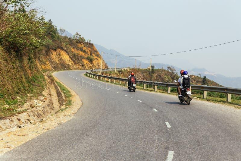 Turisti che conducono i motocicli sulla strada principale con l'arbusto e le rocce lungo la strada di estate al PA del Sa, Vietna immagine stock