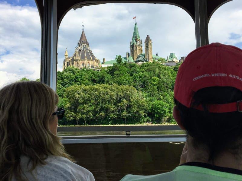 Turisti che contengono le viste della collina del Parlamento e del paesaggio urbano mentre prendendo una barca di giro attraverso immagine stock