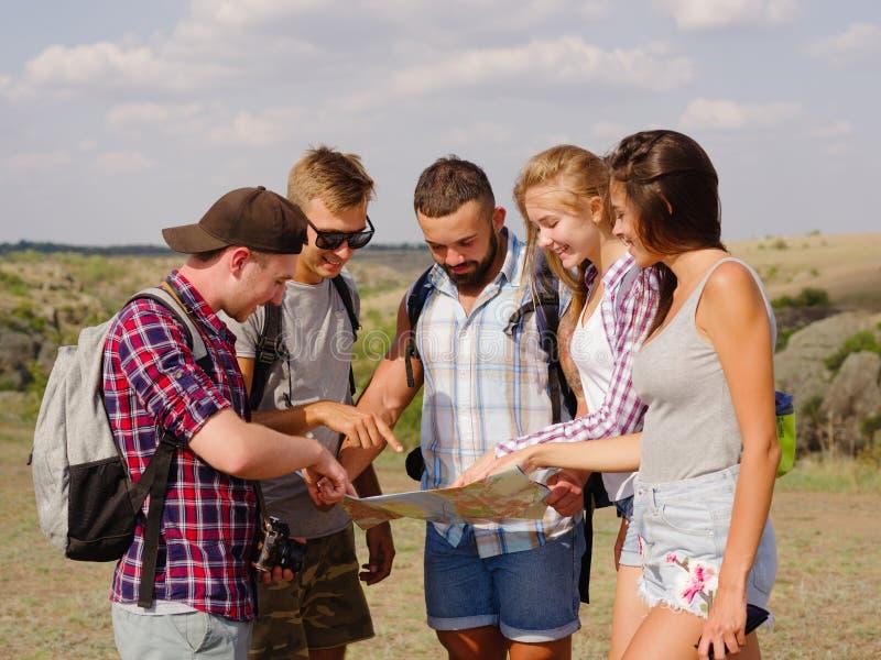 Turisti che esaminano un programma Guidi la mostra della mappa agli studenti di viaggio su uno sfondo naturale Concetto d'escursi fotografie stock