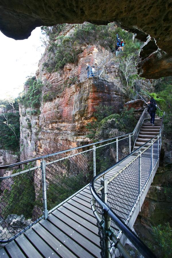 Turisti che fanno un'escursione alla traccia ripida di zigzag di grandi scala lungo la scogliera rossa del taglio della roccia co fotografia stock libera da diritti