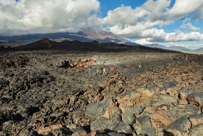Turisti che fanno un'escursione sul vulcano di Tolbachik di eruzione del giacimento di lava sulla penisola di Kamchatka, gruppo d fotografie stock