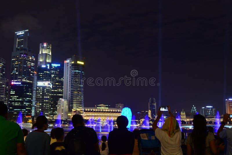 Turisti che guardano gli spettacoli di luci a Singapore fotografia stock libera da diritti