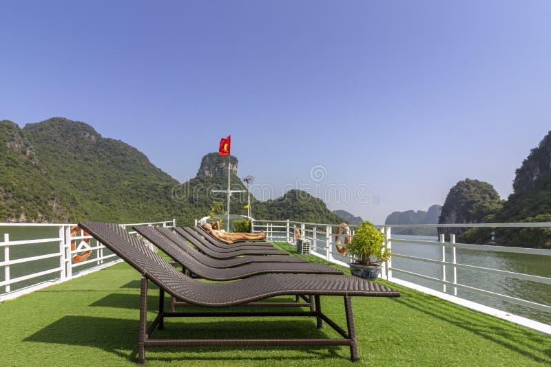Turisti che prendono il sole nel tetto della barca alla baia di lunghezza dell'ha che discende la destinazione turistica popolare immagine stock