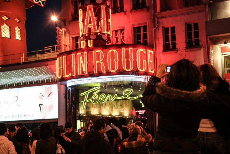 Turisti che prendono le immagini davanti a Moulin Rouge alla notte, uno dei cabaret di Pigalle più famosi ed i corridori di manif fotografia stock