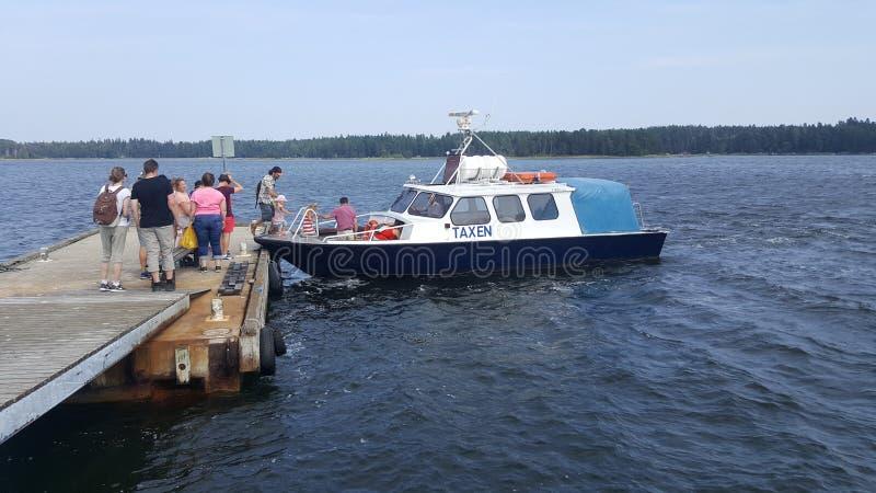 Turisti che registrano un taxi della barca nel porto della fortezza di Svartholm in Loviisa, Finlandia immagine stock libera da diritti
