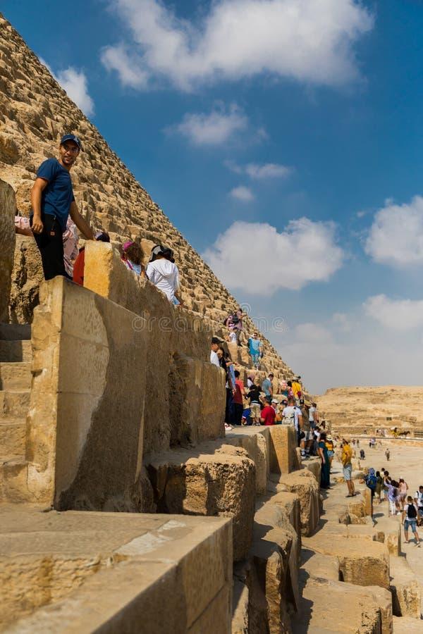 Turisti che scalano le piramidi di Giza, Egitto fotografia stock