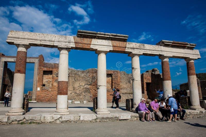Turisti che visitano le rovine del forum alla città antica di Pompei in una bella molla in anticipo fotografia stock libera da diritti