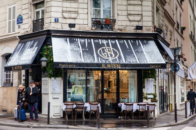 Turisti con bagagli accanto ad un ristorante italiano ad un bello angolo di Parigi nell'inverno immagini stock libere da diritti