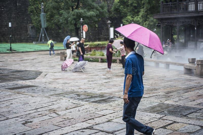 Turisti con gli ombrelli nel punto scenico piovoso immagini stock