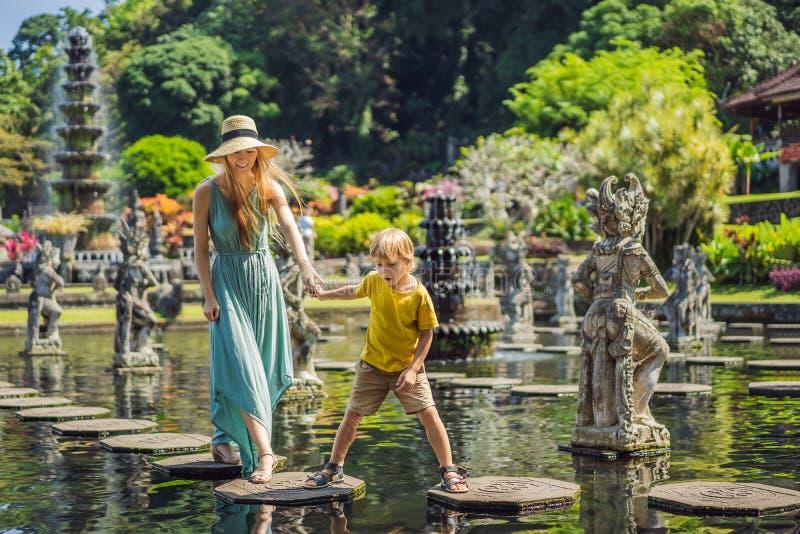 Turisti del figlio e della mamma in Taman Tirtagangga, palazzo dell'acqua, parco dell'acqua, Bali Indonesia Viaggiando con il con immagine stock